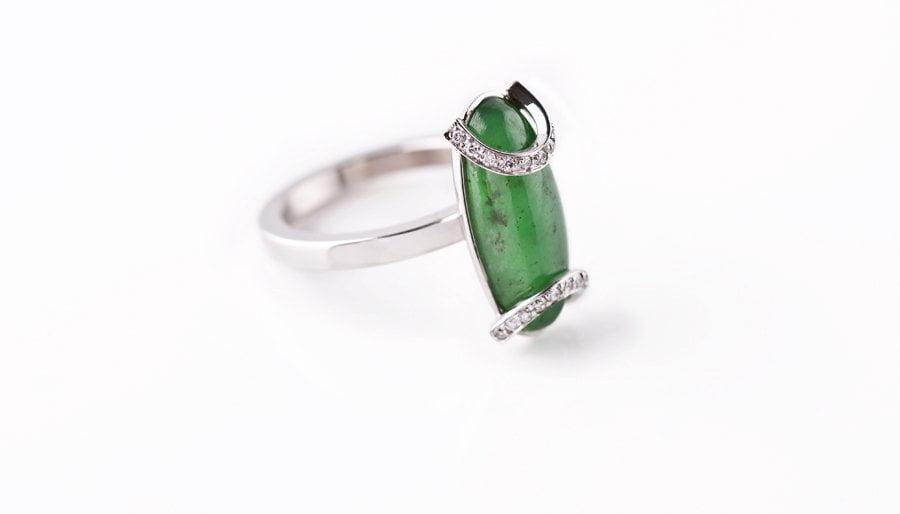 Ring i 18 k vitguld med en cabochonslipad grön grossulargranat samt  briljantslipade diamanter i två bågar. 64fc5dfa5c302